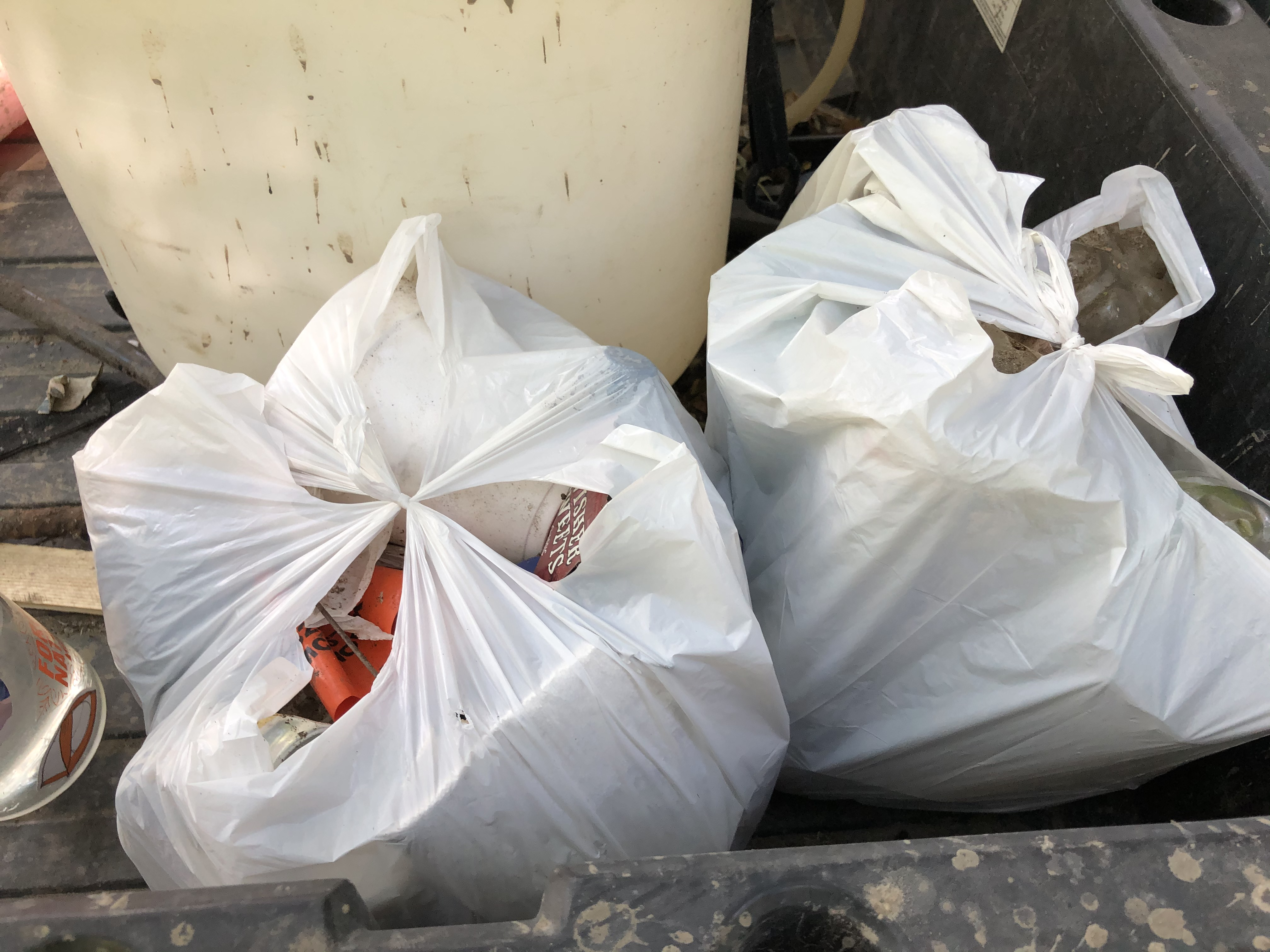 Bags of garbage in the back of the park staff truck.