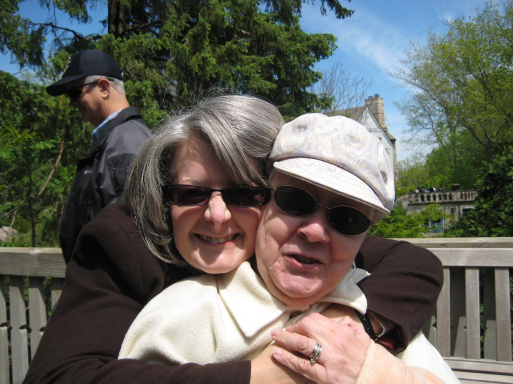 Ruth hugging her mom with her dad in the background of the photo. They are outdoors on a sunny day.
