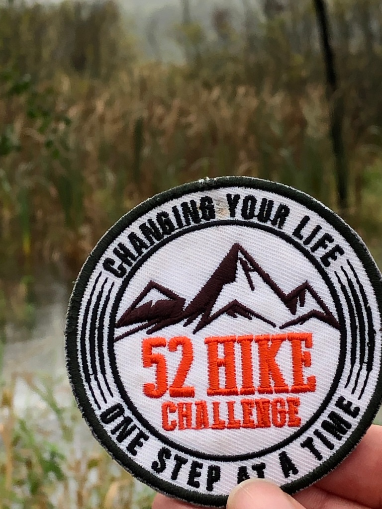 52 hike patch held against a natural background.