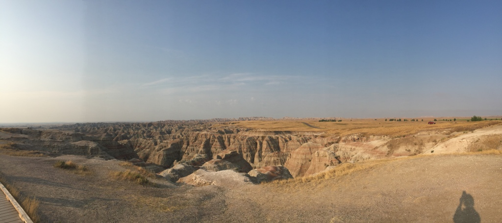 View of Badlands National Park looking into the canyon with the shadow of Ruth in the foreground.