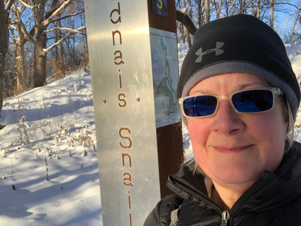 Ruth Standing next to a sign for the park Vadnais-Snail Lakes Regional Park on a sunny day for a snowshoe hike.