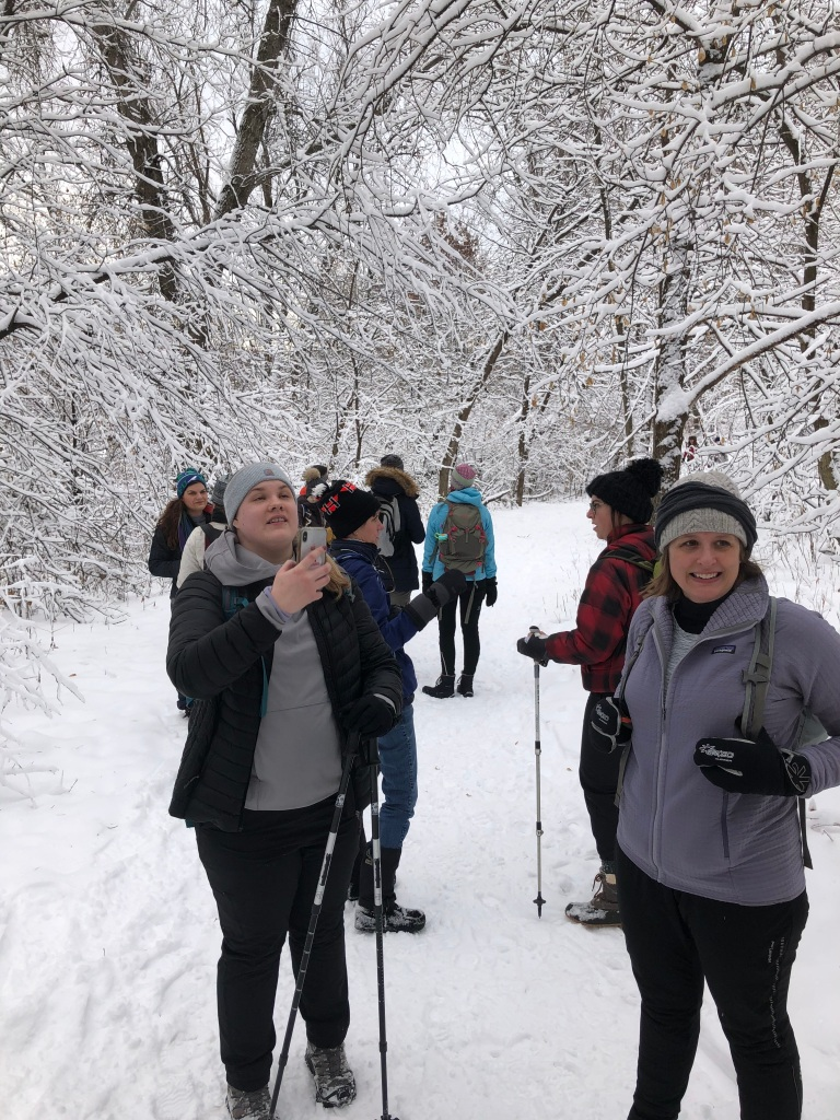 Group of women marveling at the snow covered trees while hiking.