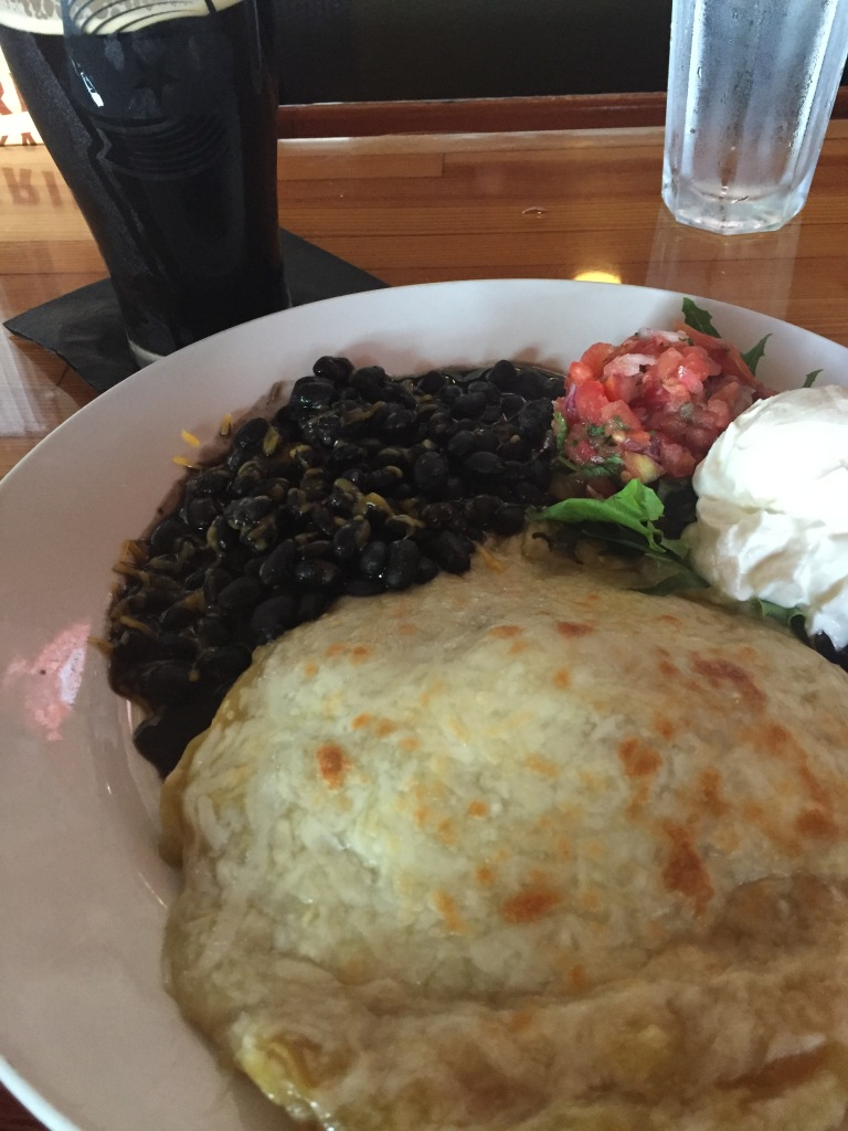 Photo of the stacked enchilada with black beans, salsa and sour cream on a plate sitting on the bar at the Gunflint Tavern, Grand Marais, Minnesota. There is a glass of dark beer and another of water in the background.
