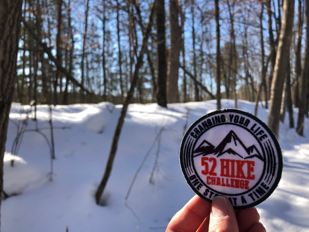 Photo of my 52 Hike Challenge patch against the background of snow and trees. The sun is shining in the background.