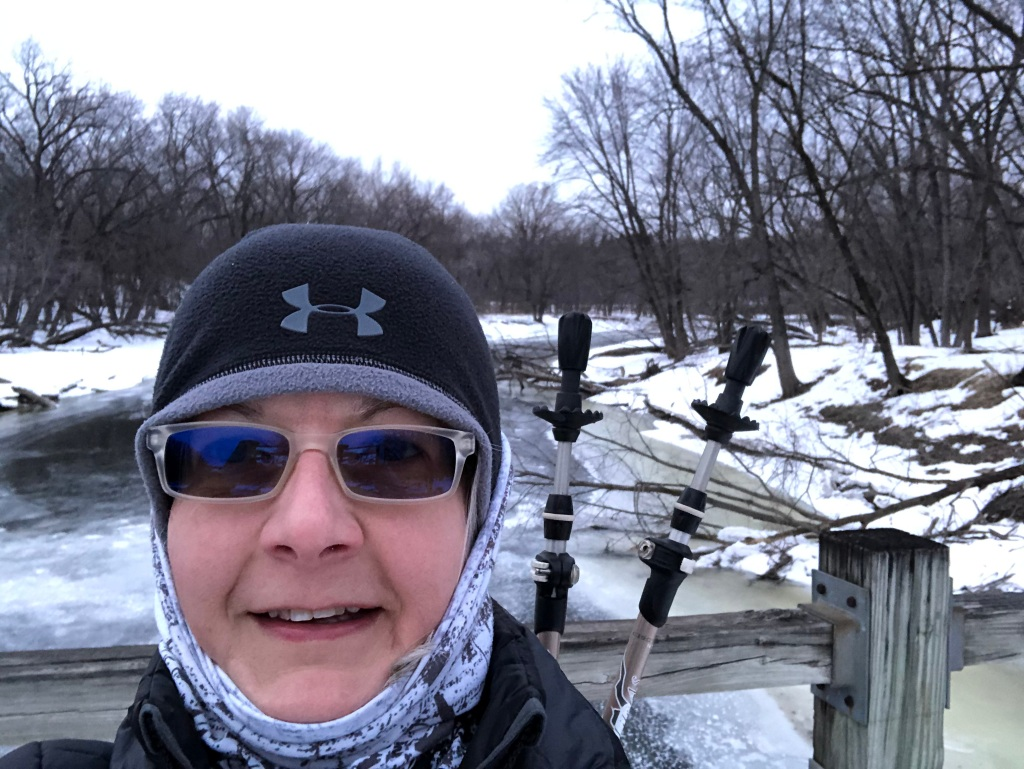 Photo of Ruth in her winter gear on a cold cay on the bridge to Pike Island at Fort Snelling State Park with the river in the background.