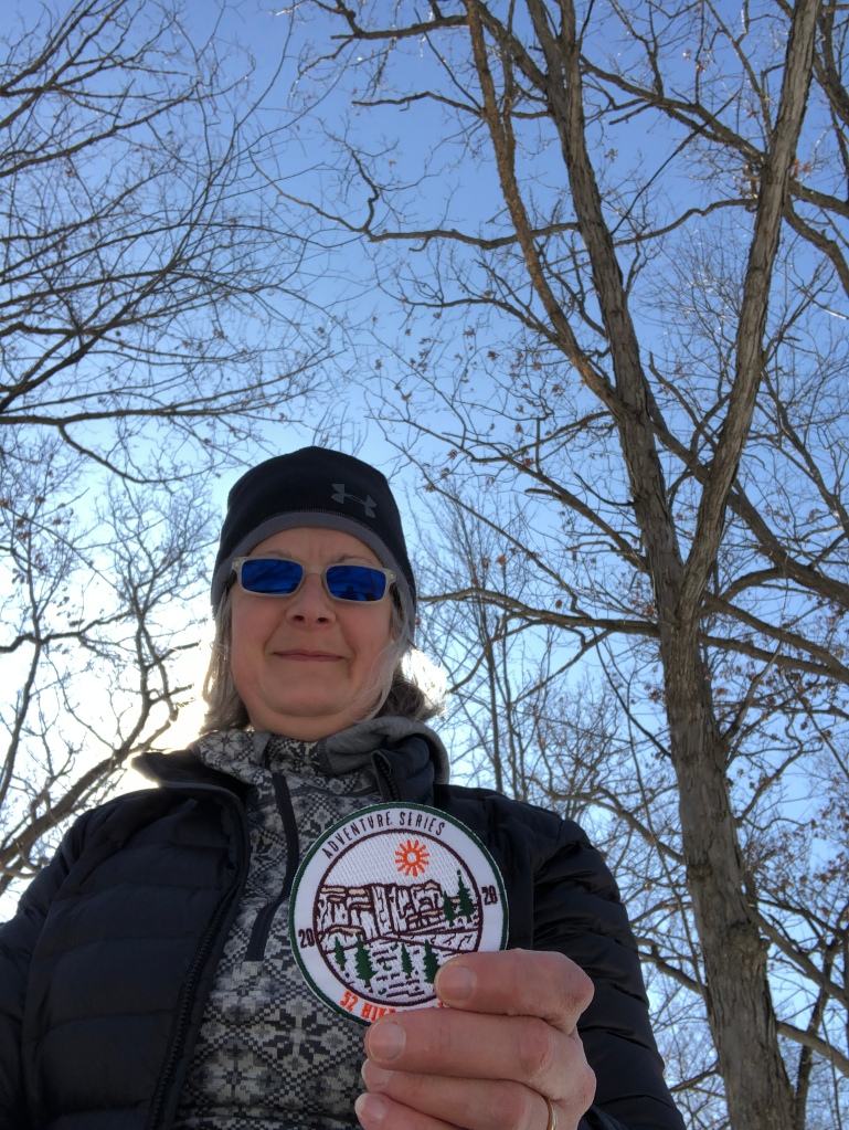 Photo of ruth holding her 52 Hike Challenge Adventure Series Patch with the sunshine behind her. She is standing in a wooded area.
