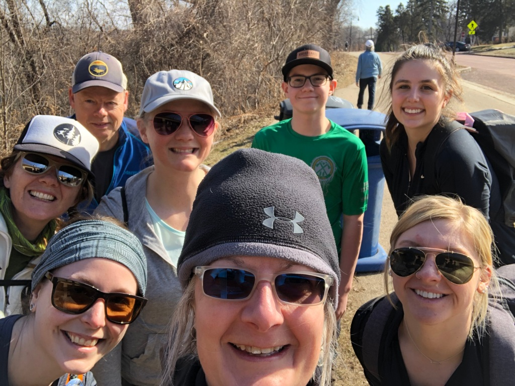 Photo of the volunteers who helped Ruth with her trail clean up efforts outside on the parkway. They are all smiling and enjoying the sun.