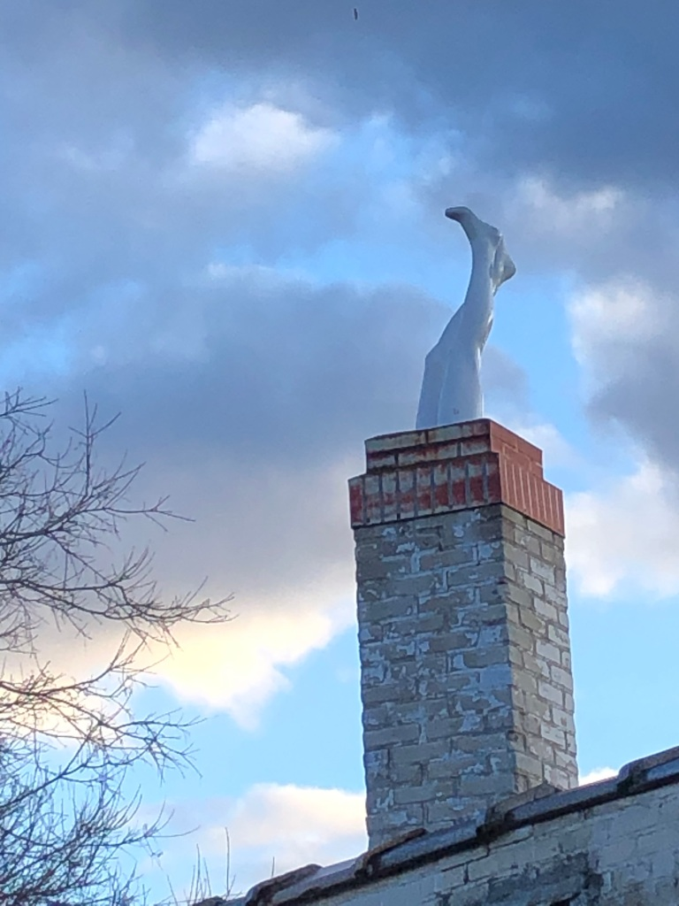 A sculpture of a pair of legs sticking out of a ventilation chimney on a building against a blue sky with clouds.