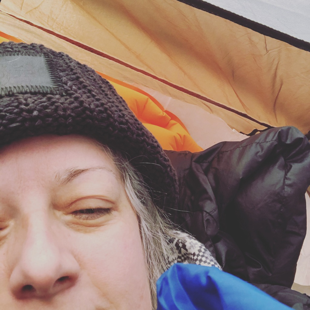A photo of Ruth inside her tent in the early morning. She is wearing a black stocking cap and is nestled into her sleeping bag.