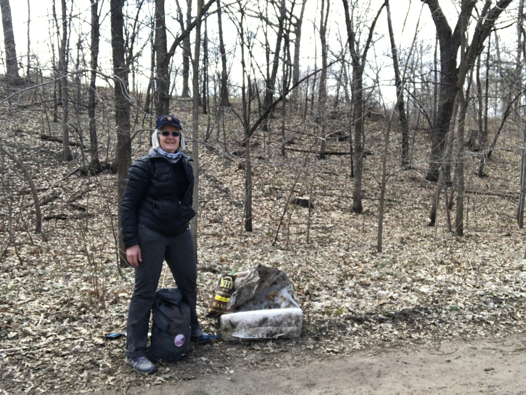 Photo of Ruth with the garbage she found while hiking. The ground is covered with leaves and early spring flowers. The trees have not yet leaved out.