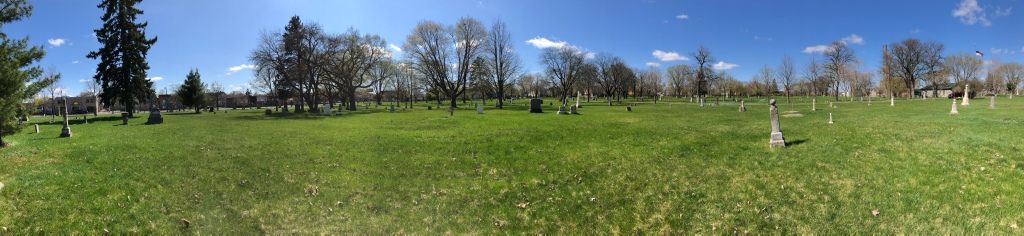 A panoramic photo of the Minneapolis Pioneers and Soldiers Memorial Cemetery taken from the cemetery grounds. There are few markers and many trees. The sky is mostly clear blue with few clouds.