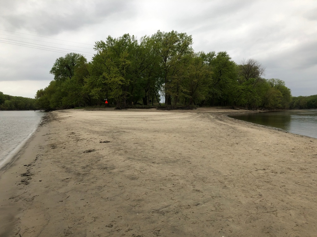 Photo of a sandy beach with the Minnesota River on the left of the image and the Mississippi River on the right side of the river. The center of the image is looking toward Pike Island which is covered in trees. The sky is cloudy with a grey cast. There is an orange triangular warning sign at the place where the sand meets the trees.