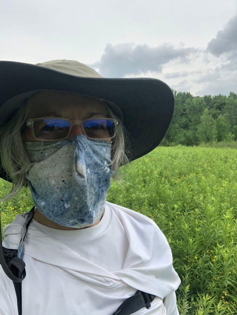 The photo is of Ruth standing on in a verdant field which is bordered by trees in the background. A few clouds dot the sky. Ruth is wearing a wide-brimmed green hat, sunglasses which are reflecting a blue tint and a blue and tan mottled facemask.