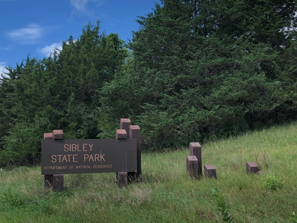 The photo has a dark brown sign with the words Sibley State Park. It is supported by posts of varying heights. The sign is in a filed with green leaved trees in the background. There is a small bit of blue sky and white clouds behind the trees.