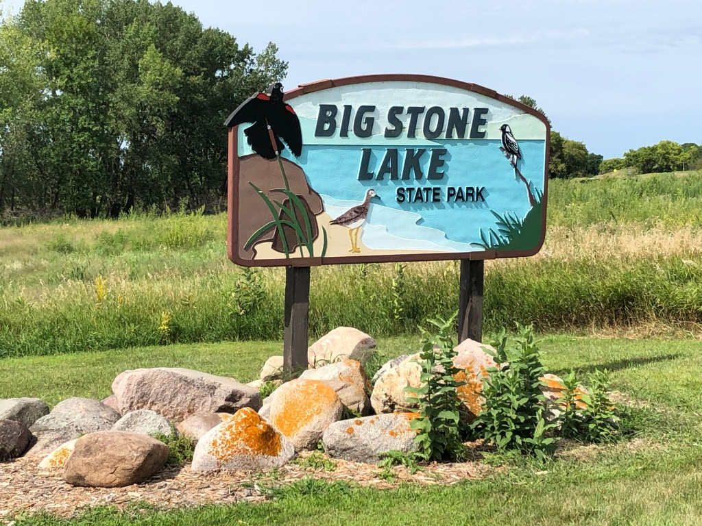 The picture has a small group of gray rocks with orange lichen and a few plants in the foreground. Above the rocks is the Big Stone Lake State Park sign that has a beach with three different species of birds. The sign is carved and painted wood. The background has a small field of grass and trees in the distance.