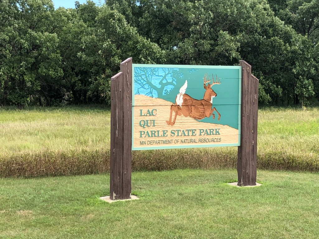 The picture has the Lac qui Parle State Park sign in the foreground on above short cut grass. The sign has a white tail deer leaping away from the carved park name with a teal background that looks like woods in the background. Behind the sign there is taller grass and further back there are trees.