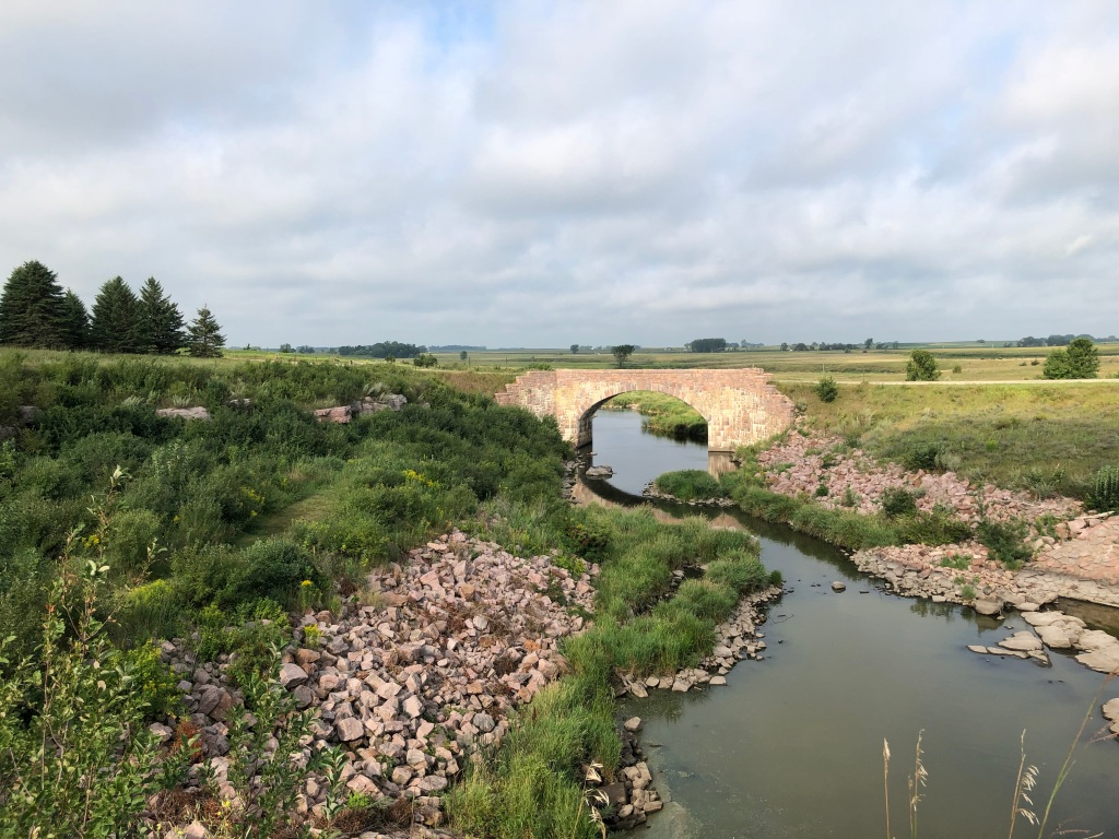 The photo is of the Split Rock Creek with a road bridge in the distance. There are pink toned rocks on the shote of the creek with grasses and flowers on the banks above. Farmland is in the background of the photo. The sky is blue with low hanging clouds.
