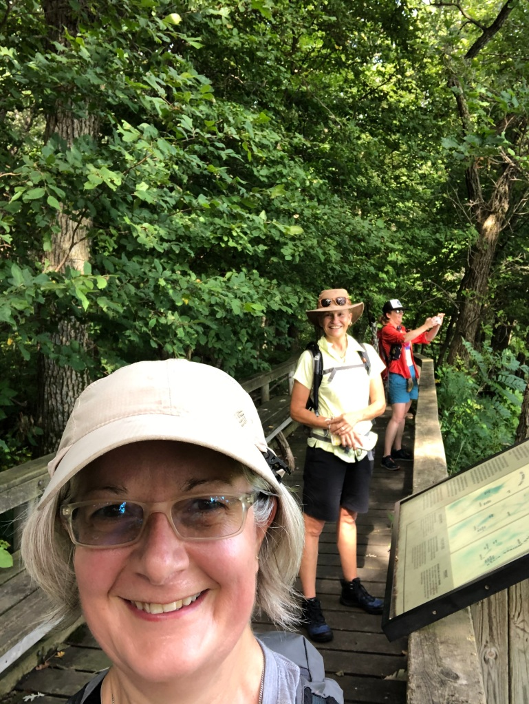 Photo of Ruth wearing a tan hat with hiking friends, Lynae and Jen in the background socially distanced at an overlook at Kilen Woods State Park.