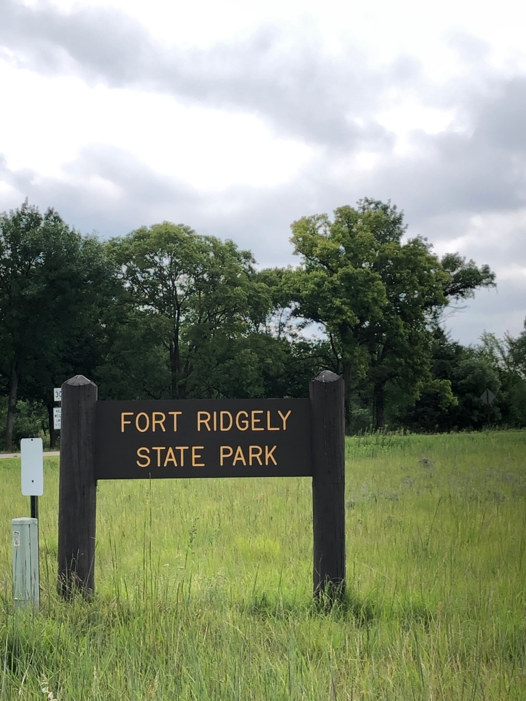 The photo has the Fort Ridgely State Park sign in the foreground. The sign is simple block letters in yellow on a brown painted background. The background has a field of prairie grass with trees in the distance.