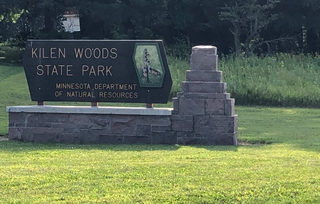 The photo is of the Kilen Wood State Park sign which has a wildflower carved in it and a stone base. There are woods in the background.