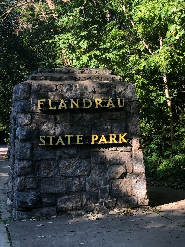 The photo shows the Flandrau State Park Sign, which is made of cut local stone in hues of brown, reds, purples and grays. The park name is  made of metal mounted to the stone face. In the background the forest provides a shaded, green field for the sign.