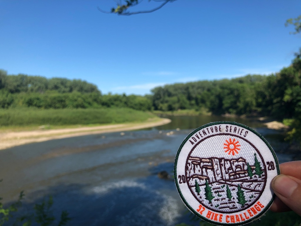 Photo has hand holding a 52 Hike Challenge 2020 Adventure Series patch. The image is focused on the patch while the out of focus background features a river and the banks with trees. The photo was taken on a sunny day.