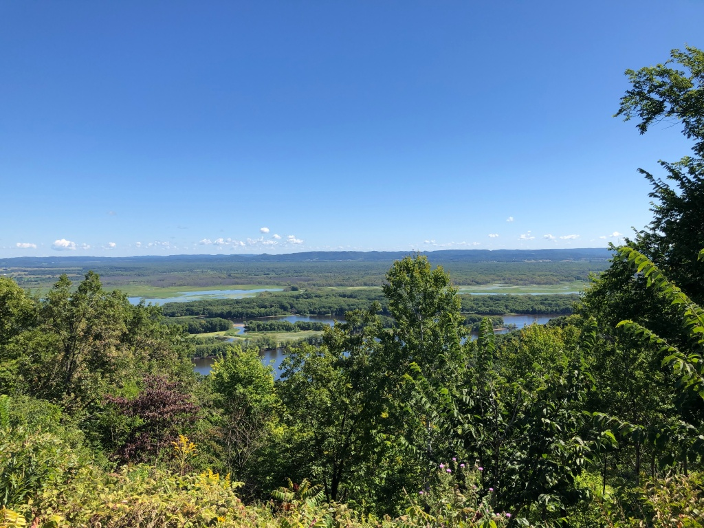 The image shows a view of the Mississippi River as it widens on its flow south and across to the landscape of Wisconsin in the distance.