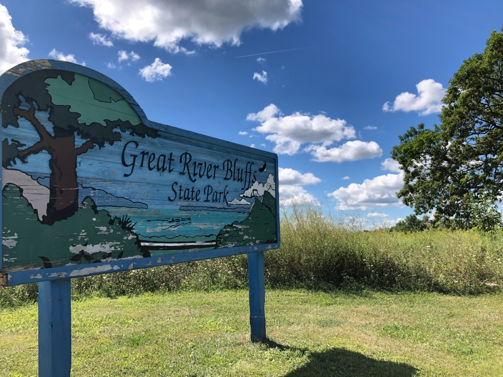 The image shows the Great River Bluffs State Park sign that is of carved wood with hills, river and trees. The paint is weathered and peeling. The sign is on mowed grass with taller grass and trees in the background. The sky is blue with clumps of white clouds.