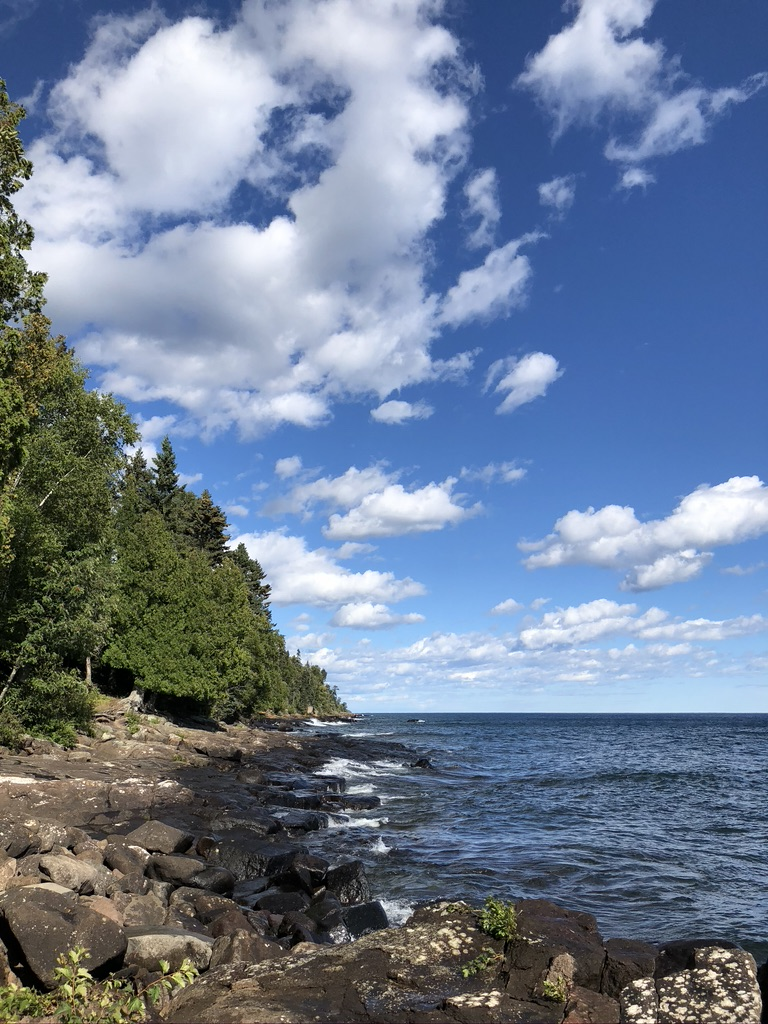The image is of the shore of Lake Superior. There is a blue sky with white clouds, the lake is a dark blue with small waves. The shore has pines standing atop the fragemented rocks typical of the North Shore area of Lake Superior on the Minnesota side of the lake.