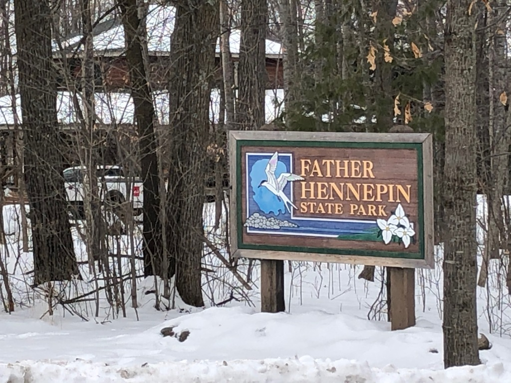 The photo is of the Father Hennepin State Park sign. The sign features an image of a Common Tern, grey rocks and white Trillium. The sign is surrounded by trees. The ground is covered in snow. In the background there is a house and truck that can be see through the trees.