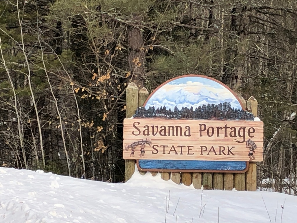 The photo is of the Savanna Portage State Park sign. The sign has images of two people portaging a canoe on the left and a person carrying a pack on the right. The top of the sign is an arch shape painted with trees and clouds. The sign has snow covered ground in front of it, trees behind.