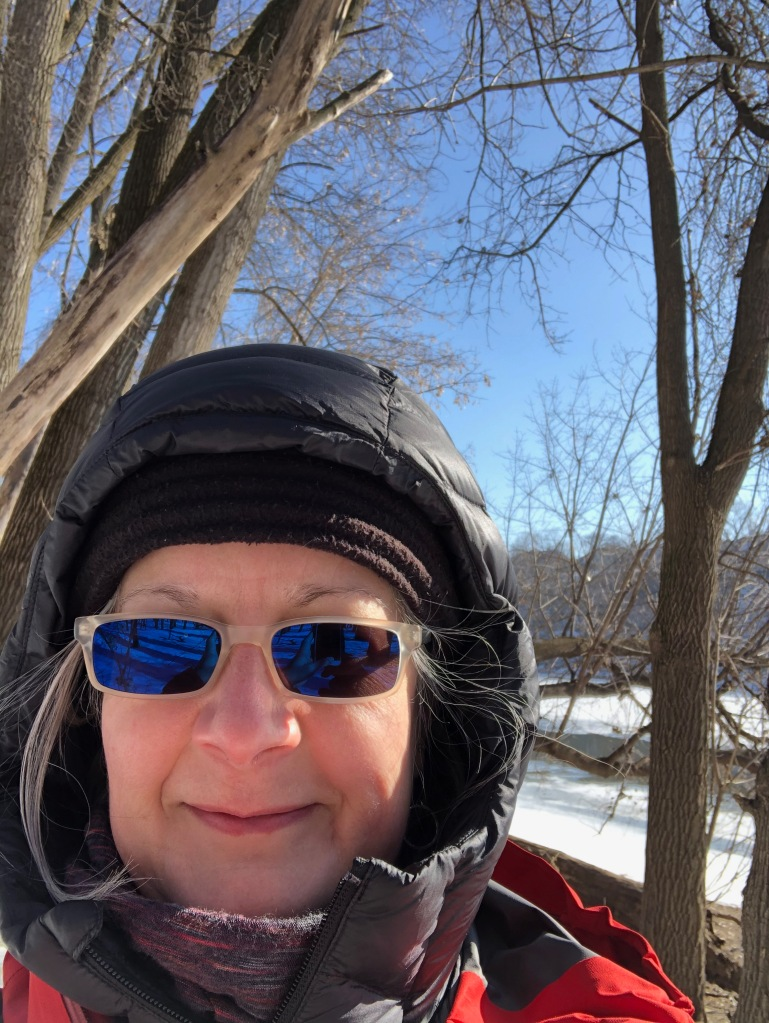 The photo is a headshot of Ruth wearing winter hiking gear and sunglasses which are reflecting blue in the bright sunlight. There are trees and water in the background.