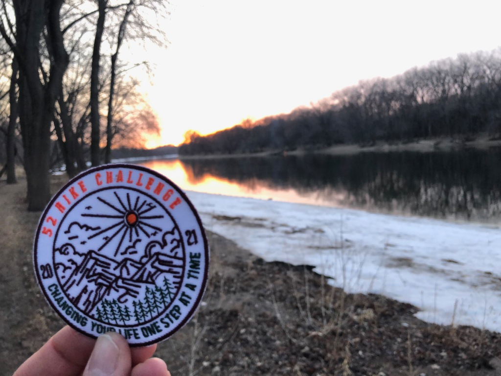 The photo shows a hand holding the 2021 52 Hike Challenge Adventure Series patch. In the background is a river with the sun setting in the distance.