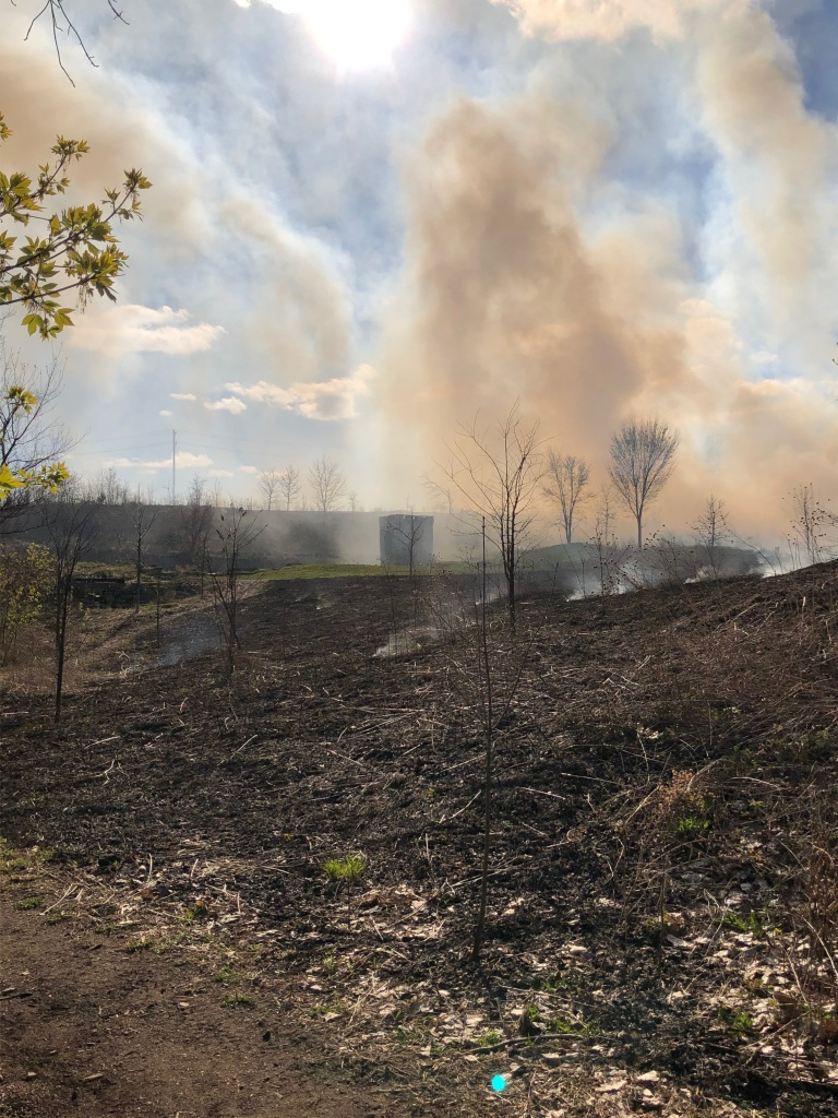 The photo shows burned ground in the foreground, smoke still rising from a few spots of smoldering grasses. The smoke slightly covers the Spring House.