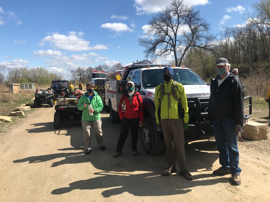 The photo is of a small group of volunteers at the park standing in front of one of the fire crew trucks. Ruth is a member of the group, wearing a red jacket.