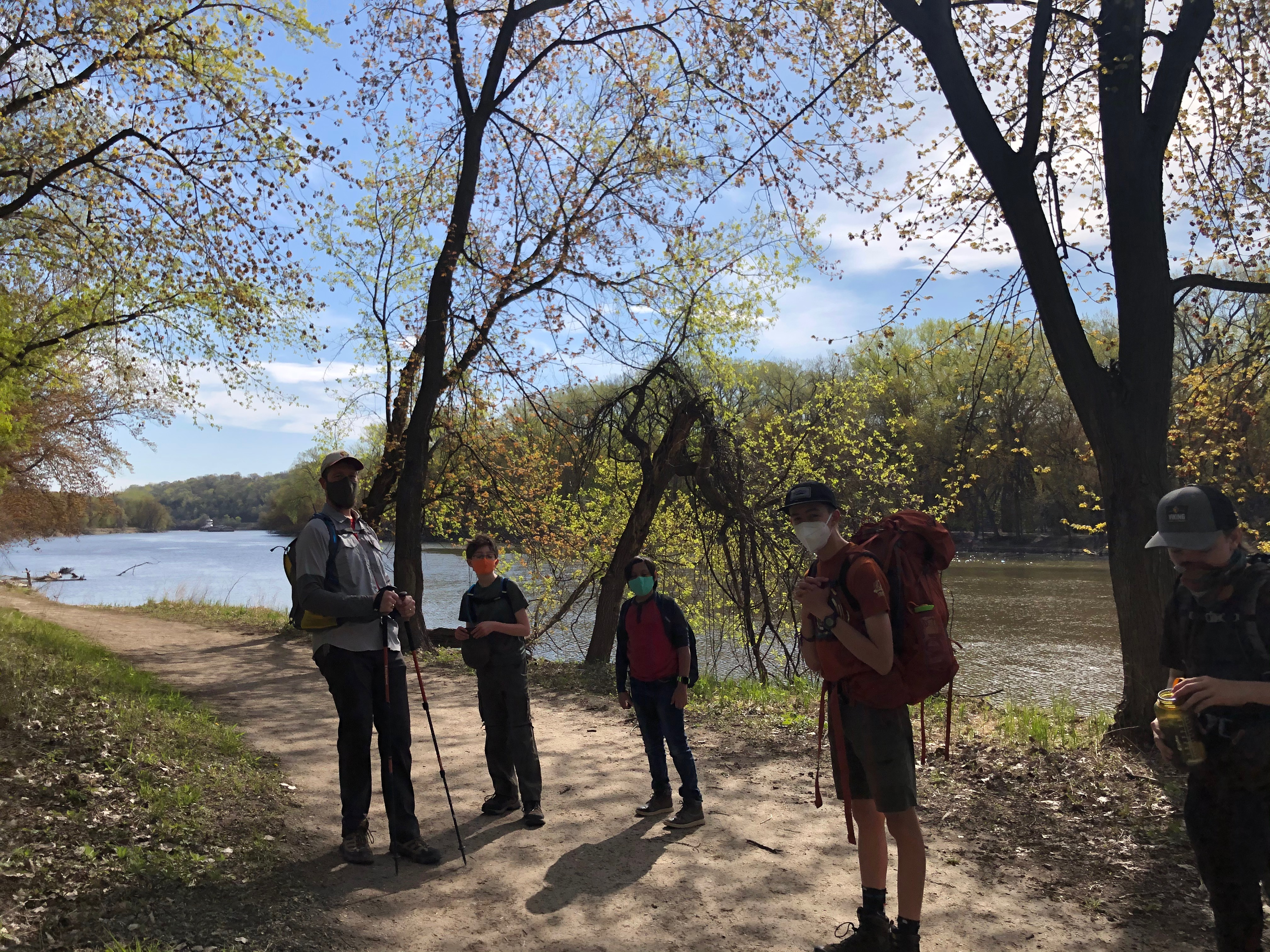 The images shows an adult hiker and four youth hikers, who are wearing masks and standing on a partially shaded trail running parallel to a river. One of the youth is wearing a large, red backpack.