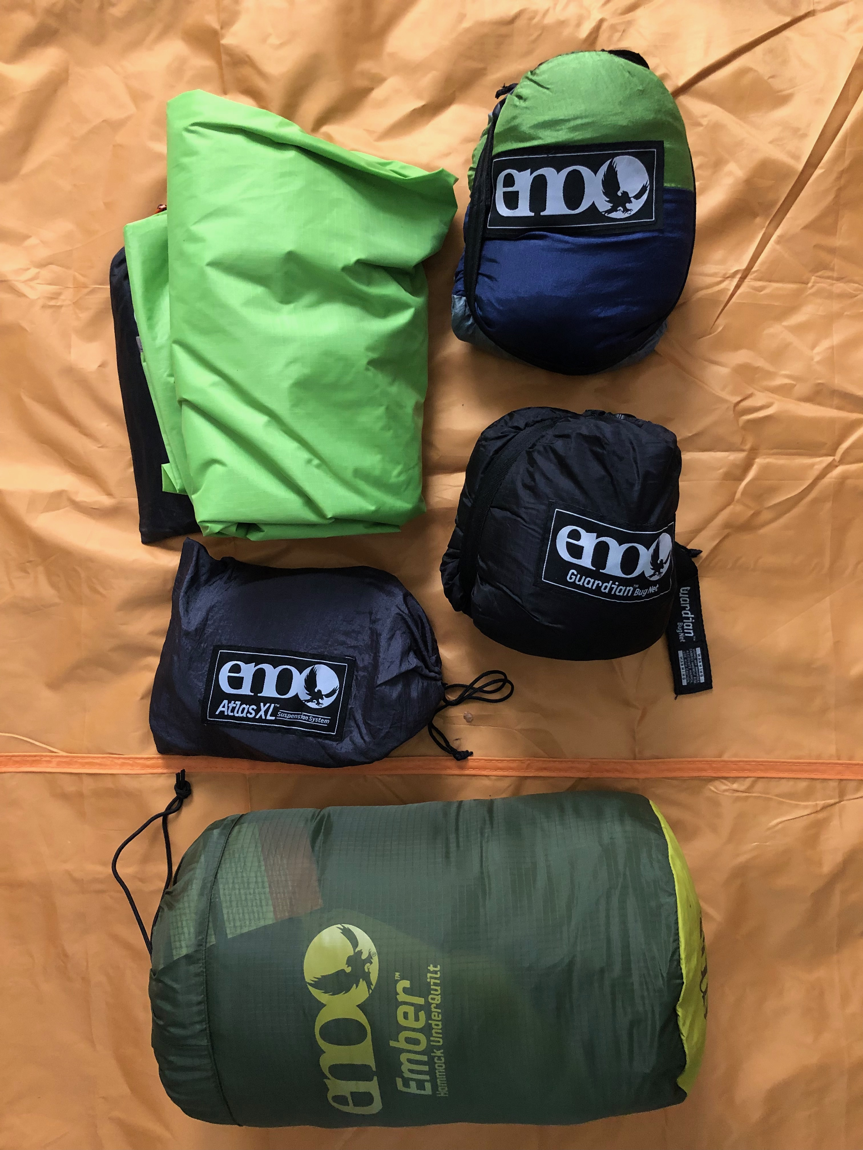The picture shows the components of her ENO Hammock system, packed into their respective storage bags. from top left to right, top to bottom are pictured the Profly™ Rain Fly, DoubleNest® Hammock, Atlas™ XL Straps, Guardian™ Bug Net, and Ember™ Underquilt on an orange background.