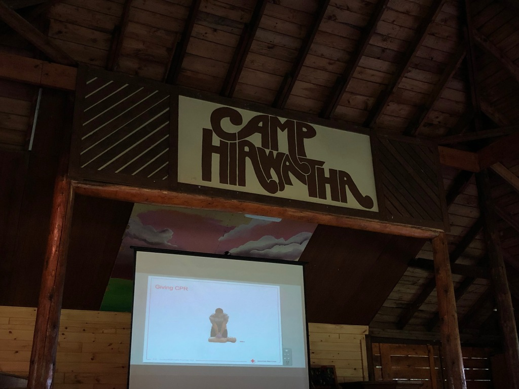 Image is of the interior of a wood building. A sign near the ceiling reads Camp Hiawatha. Below the sign is a screen on which an image from a first aid video is being projected. The room is dark.