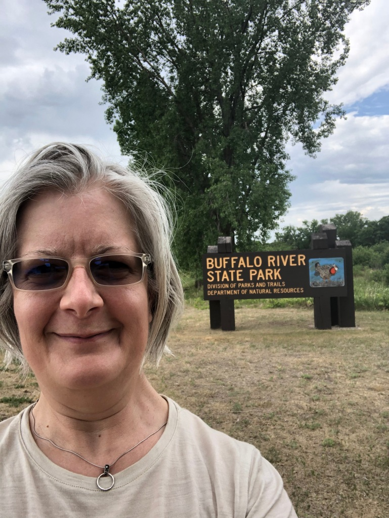 The image shows Ruth smiling while standing in front of the Buffalo River State Park sign. A large tree is directly behind her.