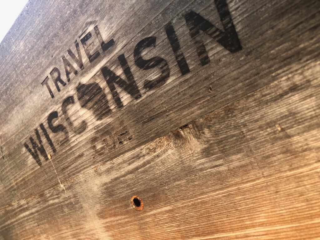 """The image is of a wooden sign with the words Travel Wisconsin burned into the weathered wood of varying shades of brown and gray. The """"o"""" in Wisconsin is in the shape of the state."""