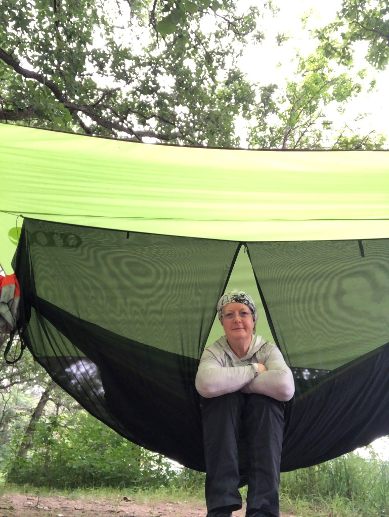 Ruth is seated under the bright green tarp of her ENO Hammock on the hammock itself. She is smiling with her arms resting on her knees while she rests.