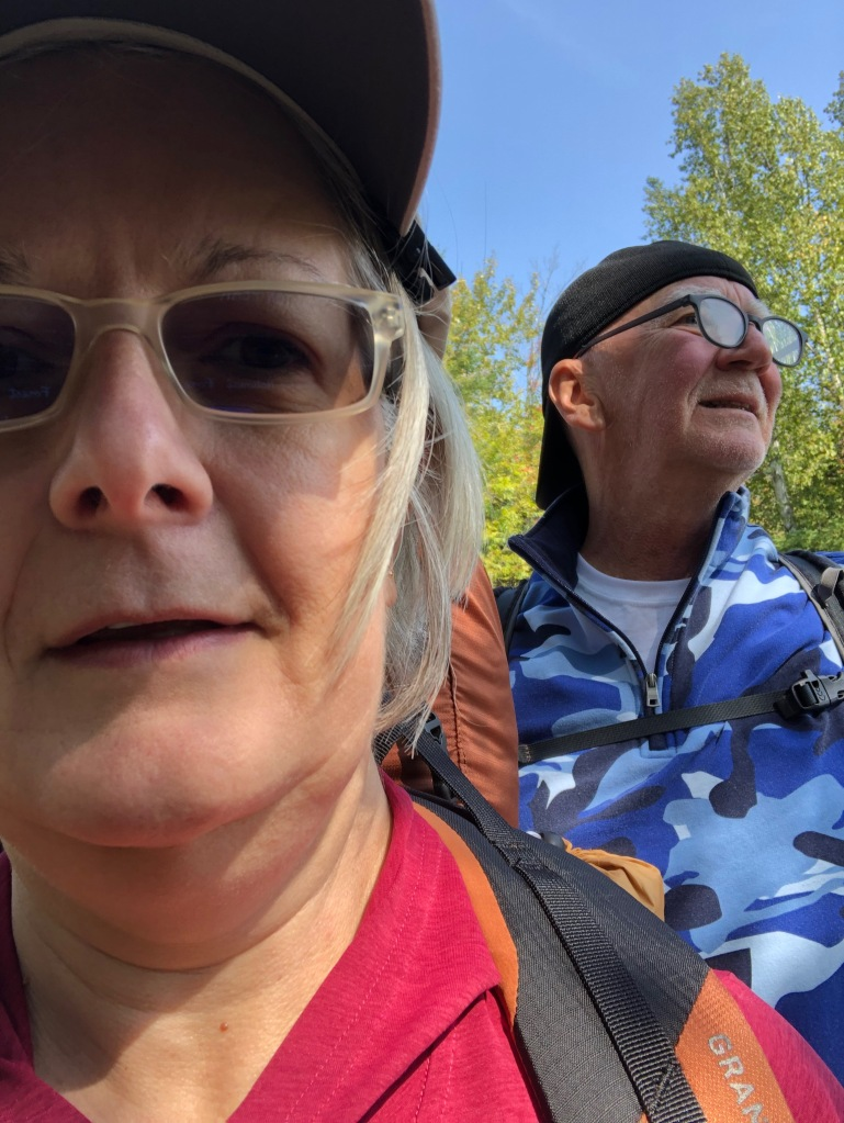 Image is of Ruth in the foreground wearing a red top and baseball cap and sunglasses. In the background, John can be seen looking off in the distance wearing a blue camouflage pullover, baseball cap and glasses.