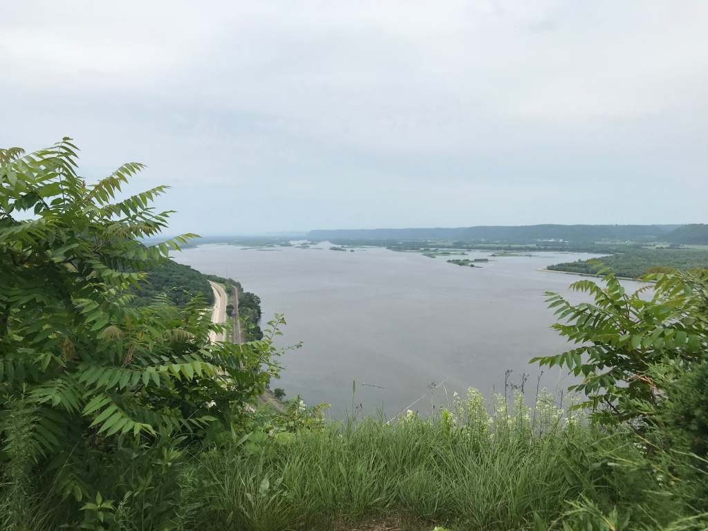 The image is taken from the top of Mount Chastity, also known as John A. Latch State Park. The image shows a view over the St. Croix river on a cloudy day. Below the trees on the bluff a road disappears into the background. Across the river, islands on the Wisconsin side of the river can be seen.